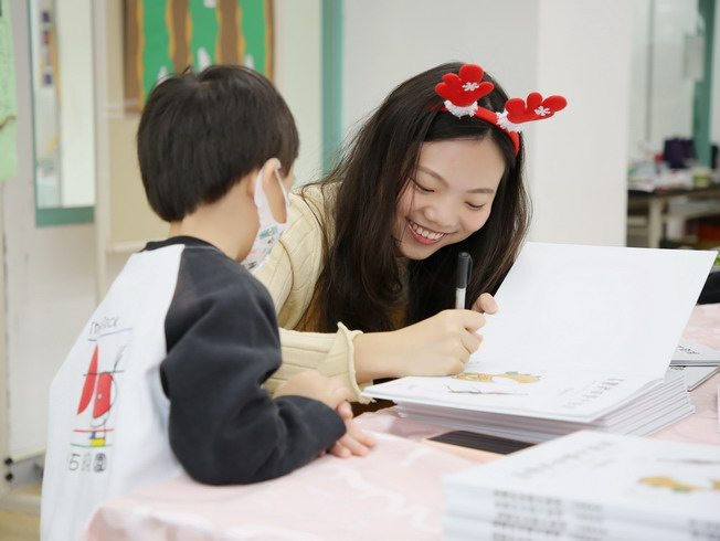 Tsai Pei-Shan, allumna of the NCYU Department of Applied Chemistry and author of the picture book, came back to her alma mater to sign new books for each pupil.