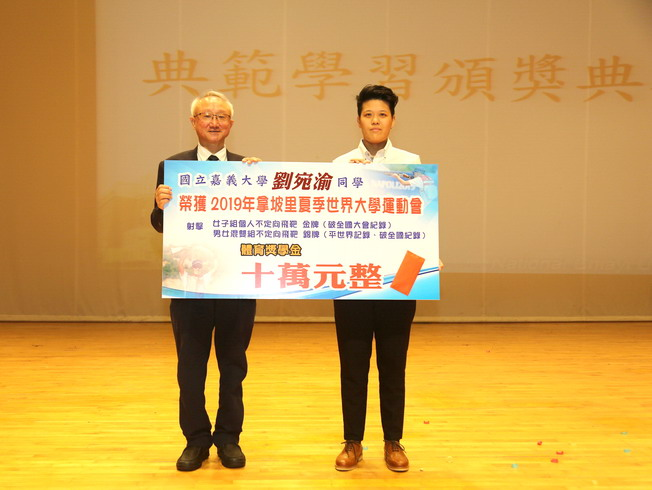 NCYU President Chyung Ay (left) presented a scholarship of NT$100,000 to Liu Wan-yu (right).