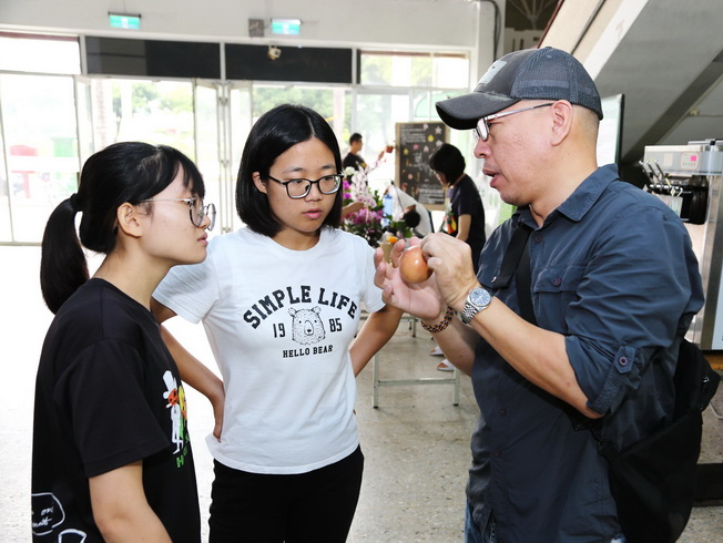 Pai-Tsang Chang, assistant professor of NCYU Department of Horticultural Science, explained tips for picking passion fruit to the visiting students.