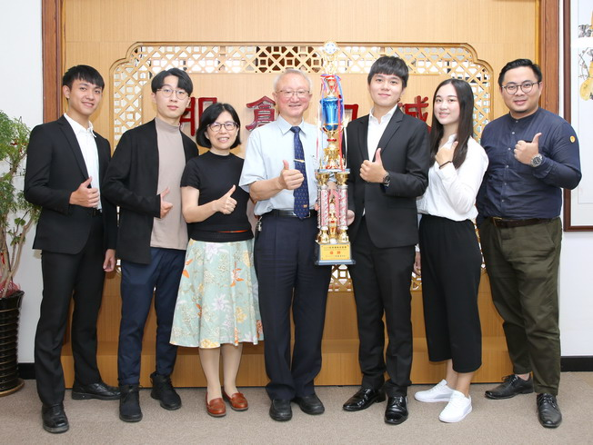 A group photo of NCYU President Chyung Ay (middle), Department of Foreign Languages Prof. Fang-Chi Chang (third from left), Plus One Innovation founder Huang Zhen-Wei (first from right) and award-winning students including Zhang Kai-Yu (third from right), Mao Yuan-Ting (second from right), Liu Yu-Kai (second from left) and Lin Wei-Hong (first from left)