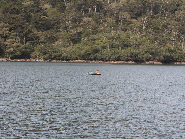 The researchers sat on the rubber boat, measuring the water depth of Daguei Lake with sonar.