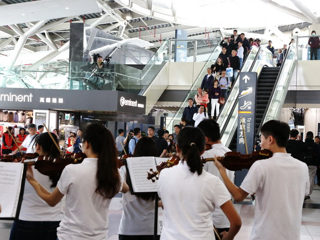 The passengers walking out of the exit were pleasantly surprised by the flash mob event.