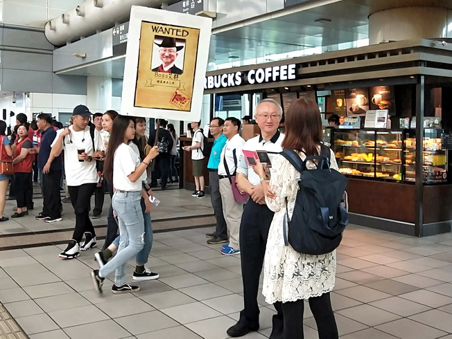 "During the interactive game ""treasure hunt,"" a sign reading ""WANTED"" with a photo of NCYU President Chyung Ay was hoisted for the participants to search for the president."