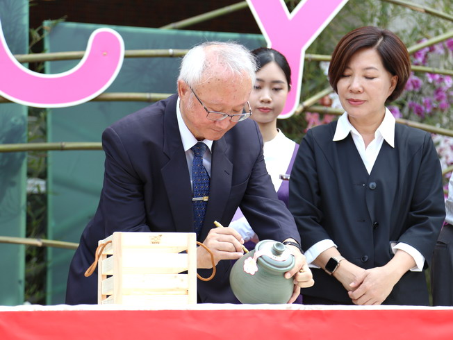 Witnessed by Deputy Mayor Chen Shu-hui (right), NCYU President Chyung Ay (left) signed on the earthenware pot.